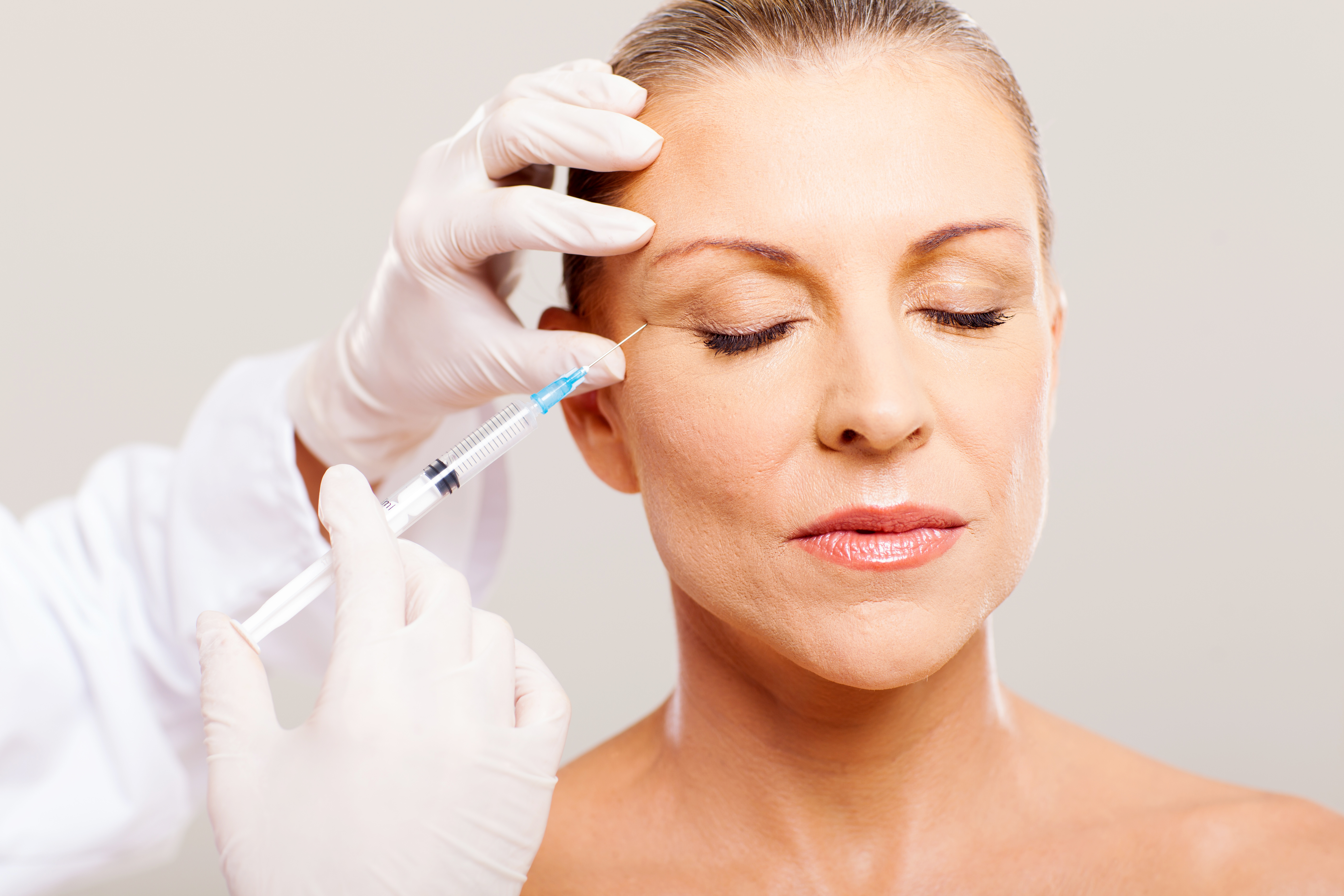 Older woman having anti wrinkle injection procedure done