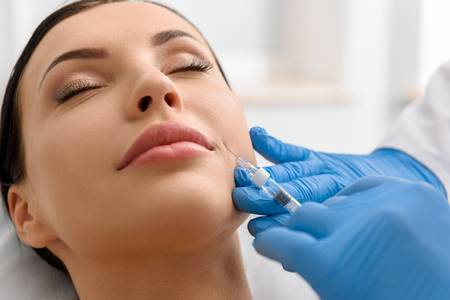 beautiful woman getting cheek fillers injected into face
