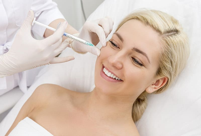 beautiful smiling woman having dermal fillers injected by skin professional