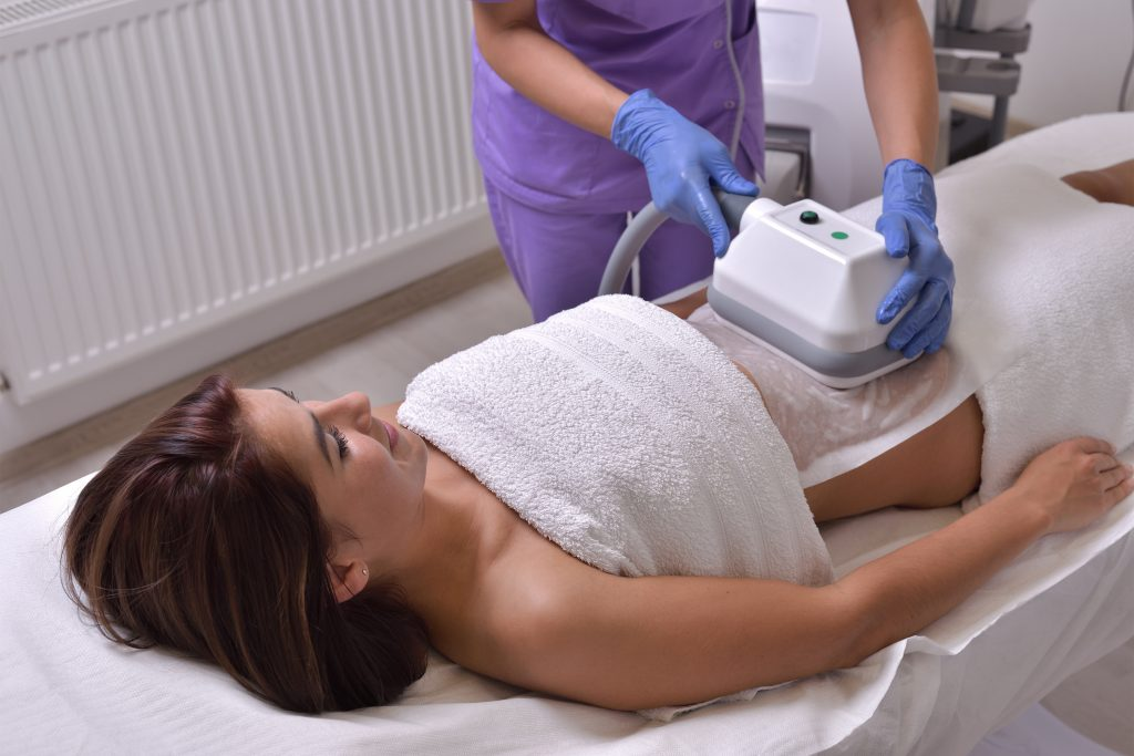 Woman having cryolipolysis or fat freezing procedure done on her stomach and abdominal area
