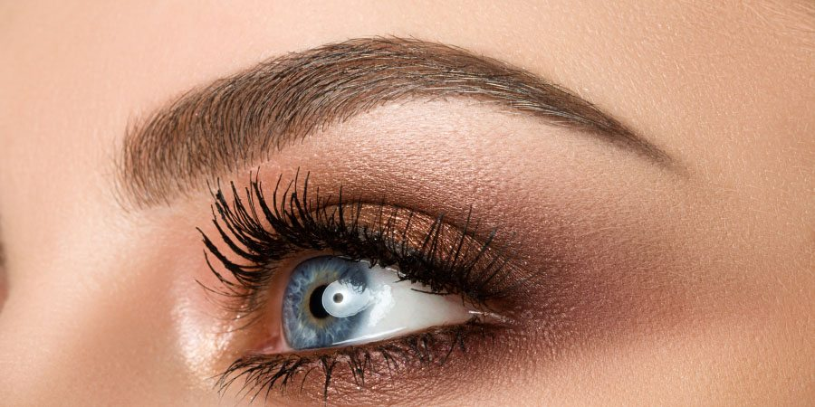 close up shot of beautiful woman with blue eyes and defined eyebrows